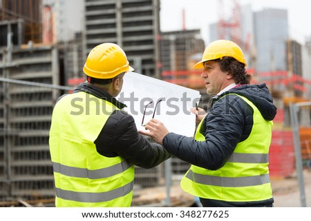 Construction worker with yellow hardhat and safety jacket checking blueprint with an architect - stock photo