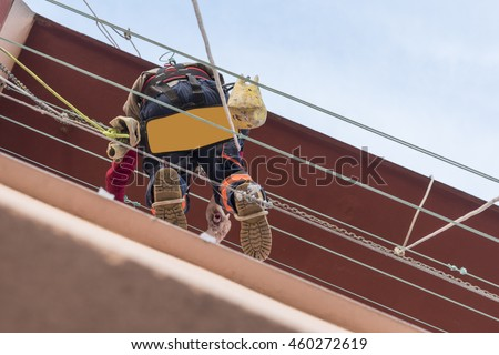 CONSTRUCTION WORKER WORKING AT HEIGHT REPAIRING A FACADE