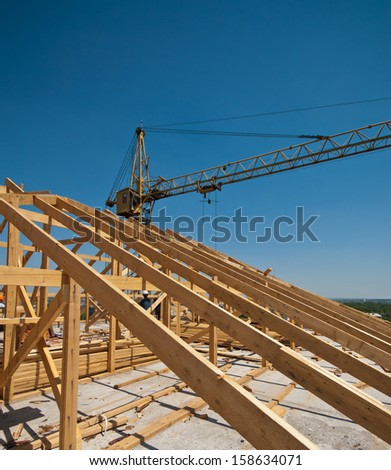 Construction worker working on the installation of a timber frame house roof and crane - stock photo