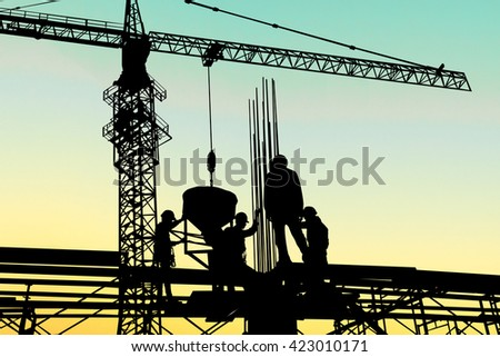 Construction workers and engineers working on high security near the tower crane. Heavy industry and Safety at Work concept. - stock photo