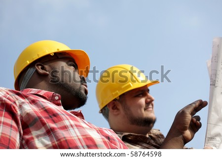 Construction workers at building site - stock photo