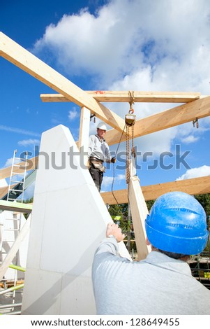 construction workers at work with wooden  roof construction of a new home - stock photo