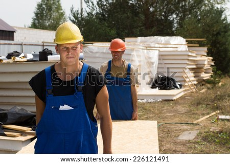 Construction workers carrying insulated wooden wall panels on a building site approaching the camera - stock photo