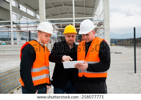 Construction workers checking the blue print on tablet - stock photo
