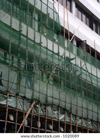 Construction workers climbing onto bamboo scaffolding in Hong Kong - stock photo