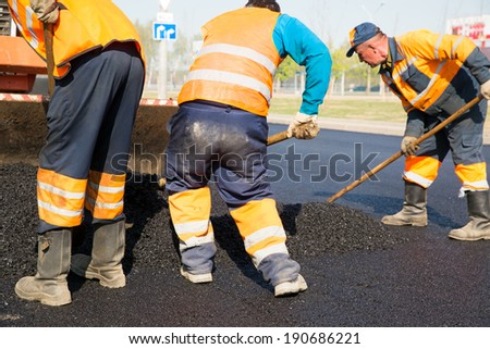 Construction workers during asphalting road works - stock photo