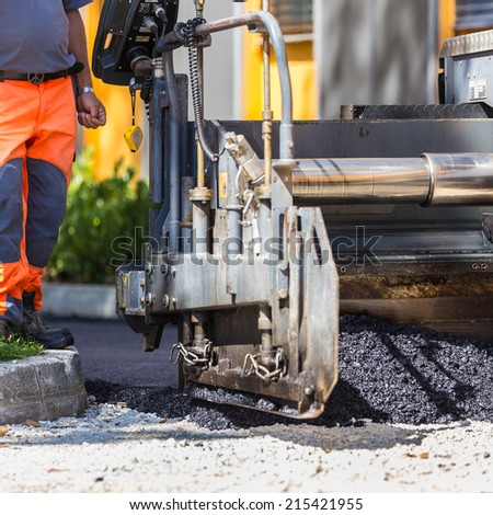 Construction workers during asphalting road works. Manual labor. - stock photo