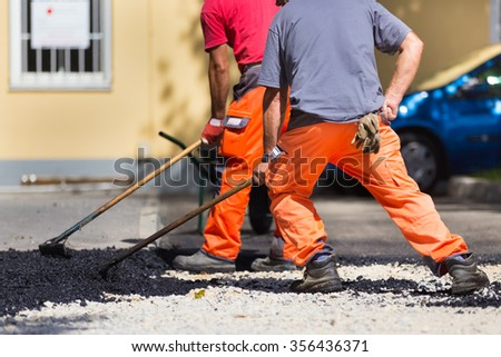 Construction workers during asphalting road works wearing coveralls. Manual labor on construction site. - stock photo