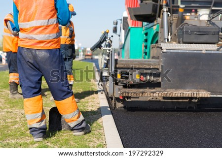 Construction workers during road works with asphalt pavement machine - stock photo