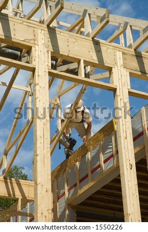 Construction workers framing the roof of a country house with help of a crane in a rural country of Quebec, Canada