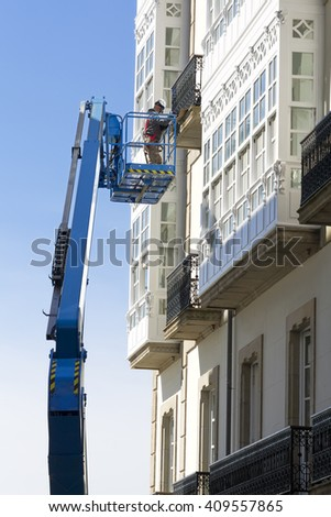 construction  workers in bucket of  crane vehicle for restore the facade of antique building