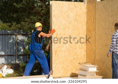 Construction workers installing insulated wooden prefab walls in the corner of a new build home on a building site - stock photo