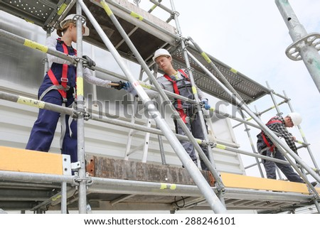 Construction workers installing scaffolding on site - stock photo