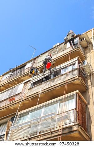 Construction workers on a high wall of an old building under the reconstruction - stock photo