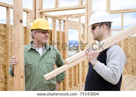 Construction Workers on the job building a home - stock photo