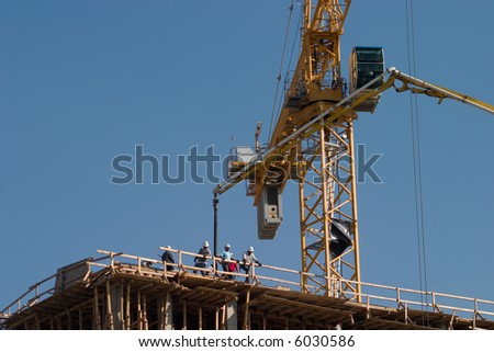 Construction workers on top of a building being built using a crane to hoist. - stock photo