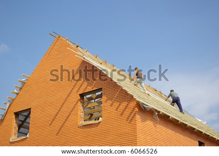 Construction workers placing the first section of roof on a new home under construction.