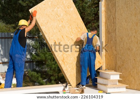 Construction workers positioning timber wall panels in a new build prefabricated wooden house - stock photo