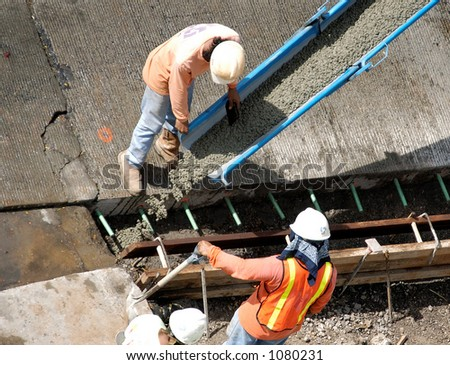 Construction workers pour cement for sidewalk Honolulu Hawaii. (image contains noise) - stock photo