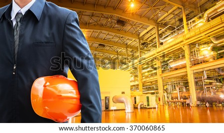 construction workers with orange helmets at work place in a factory - stock photo