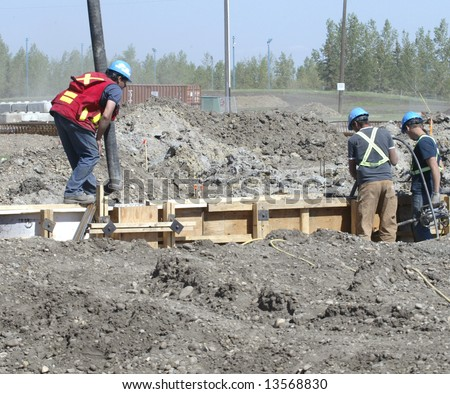 Construction workers work on a foundation for a new building. - stock photo