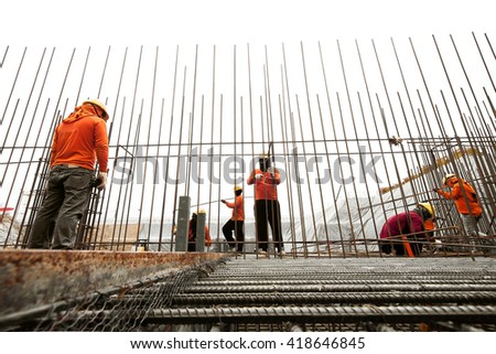 Construction workers working on steel rods used to reinforce concrete - stock photo