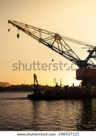 Construction works in the sea at sea platform with a floating crane. Skyline with silhouette of marine crane platform in pier. Industrial landscape - sea port at sunset. - stock photo