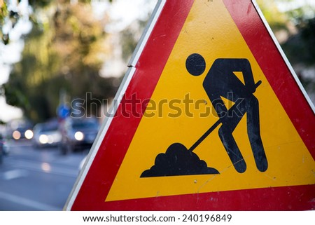 Construction zone sign by the road in urban environment  - stock photo