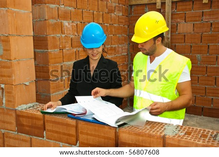 Constructions workers looking on  blueprints and folders in an unfinished house with  bricks wall - stock photo