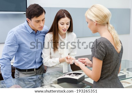 Consultant helps couple to choose jewelry at jeweler's shop. Concept of wealth and luxurious life - stock photo