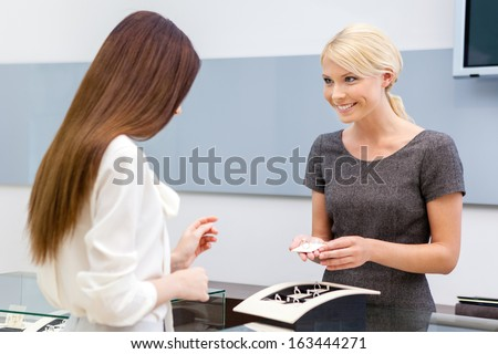 Consultant helps lady to choose jewelry at jeweler's shop. Concept of wealth and luxurious life - stock photo