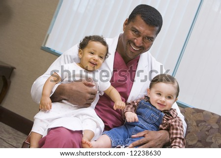 Consultant holding two IVF conceived children - stock photo