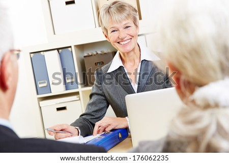 Consultant in bank giving financial advice zu senior couple - stock photo