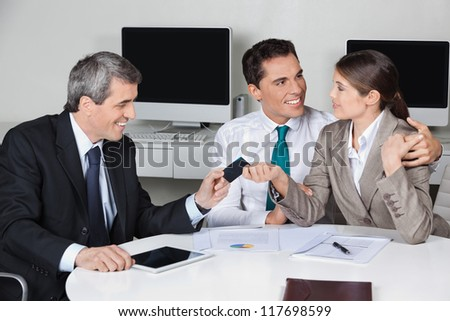 Consultant in his office offering business card to couple - stock photo