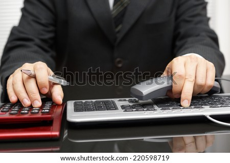 Consultant is working on computer and calling client - stock photo