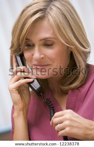 Consultant phoning client from surgery with good news - stock photo