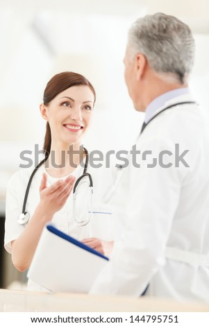 Consulting with a colleague. Young female doctor standing in front of her mature colleague gesturing and smiling
