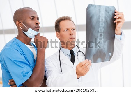 Consulting with colleague. Two confident doctors examining x-ray image - stock photo