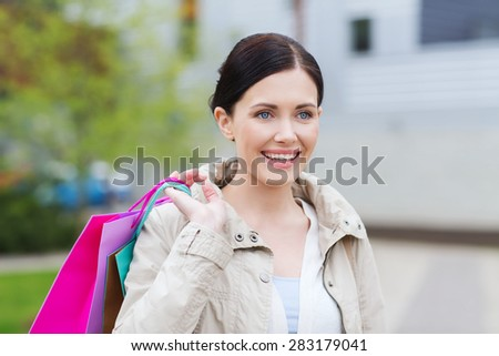 consumerism, leisure and people concept - smiling woman with shopping bags coming from sale in park
