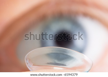 Contact lens before blue eye. Extremely close-up - stock photo