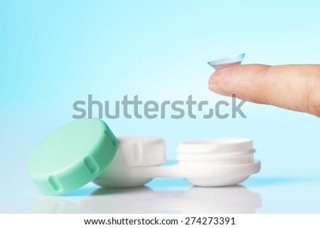 contact lens on finger and case - stock photo