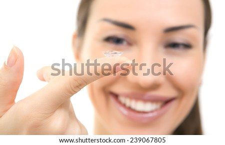 Contact lens on finger of young woman; closeup portrait. Young brunette woman holding contact lens on finger in front of her eye - stock photo