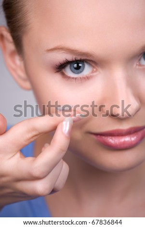 contact lens on finger of young woman looking on camera