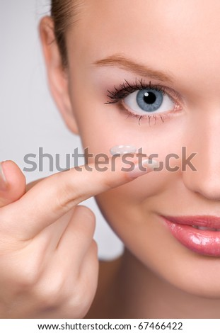 contact lens on finger of young woman looking on camera; closeup portrait - stock photo