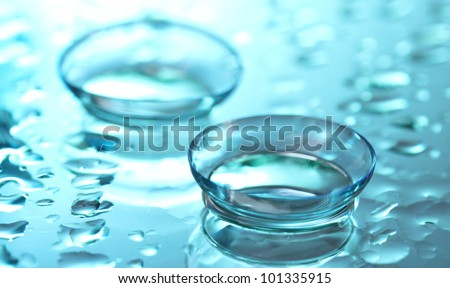 contact lens with drops on blue background - stock photo