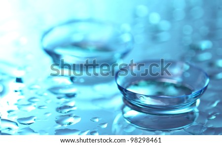 contact lens with drops on blue background