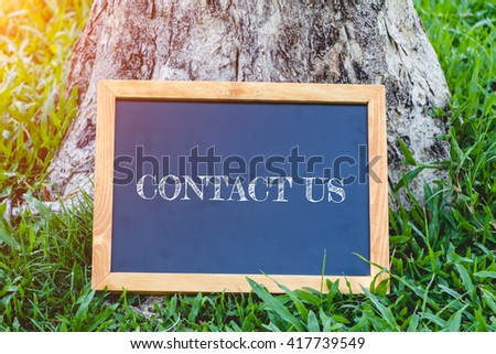 contact us concept ,Blackboard on a natural backdrop - stock photo
