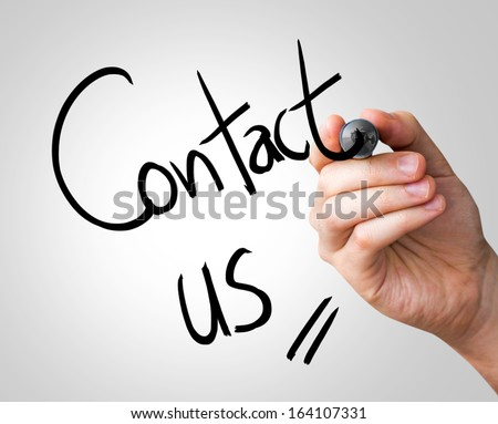 Contact us hand writing with a black mark on a transparent board - stock photo