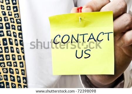 Contact us post it in business man hand - stock photo