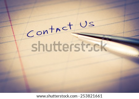 Contact us, sign in the notebook by pen. Image in cold toning - stock photo